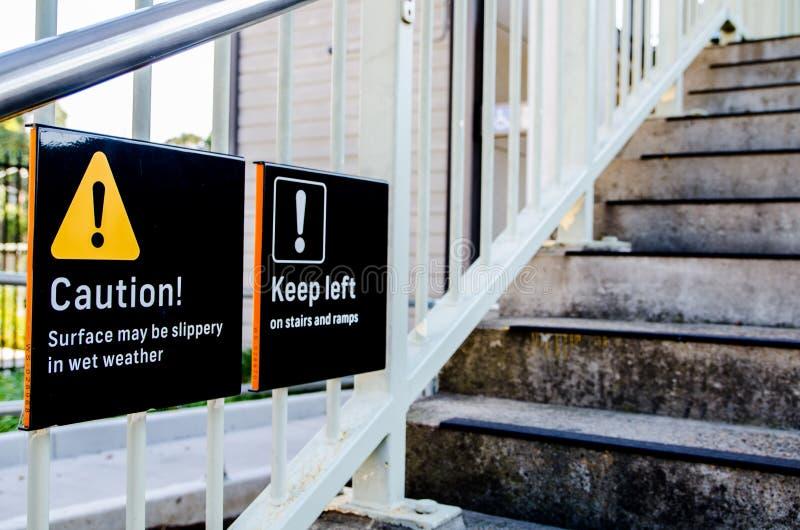 Varningstecknet på momenten för yttersida kan vara halt i vått väder och hålla vänstert på trappa och ramper royaltyfri fotografi