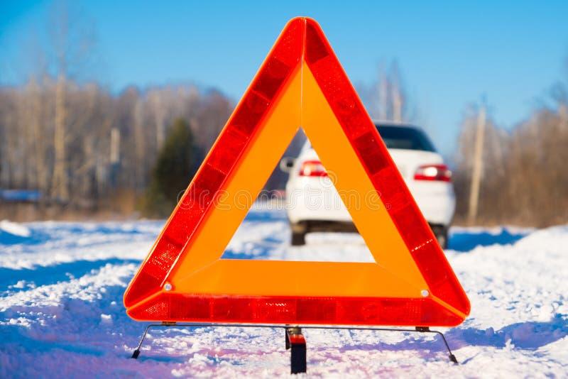 Varningstriangel och vitbil på vinterlandsvägen royaltyfria bilder