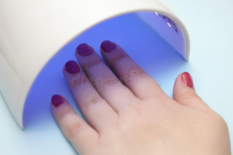 varnish on the nails, the ultraviolet lamp dries the gel lacquer royalty free stock photos
