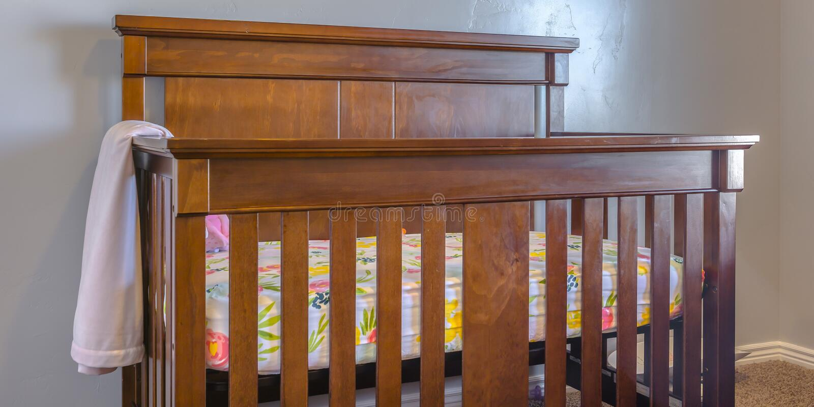 Varnished wooden crib inside a nursery stock photography