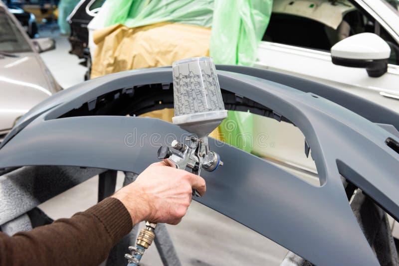 Varnisher professionnel de voiture au travail dans une station service - atelier de réparation de voiture de Serie image libre de droits