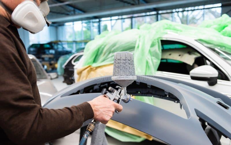Varnisher professionnel de voiture au travail dans une station service - atelier de réparation de voiture de Serie photographie stock libre de droits