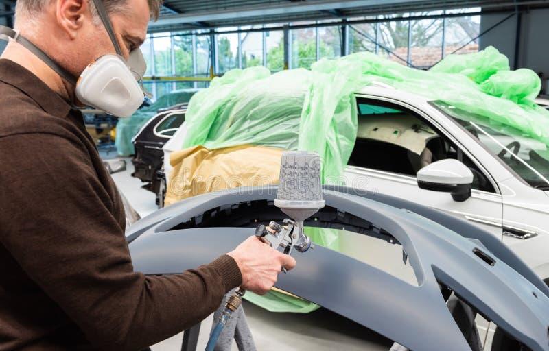 Varnisher professionnel de voiture au travail dans une station service - atelier de réparation de voiture de Serie images libres de droits