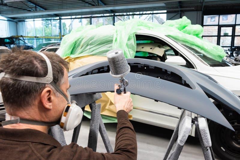 Varnisher professionnel de voiture au travail dans une station service - atelier de réparation de voiture de Serie photographie stock
