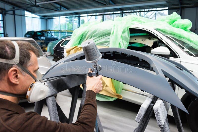 Varnisher professionnel de voiture au travail dans une station service - atelier de r?paration de voiture de Serie photo stock