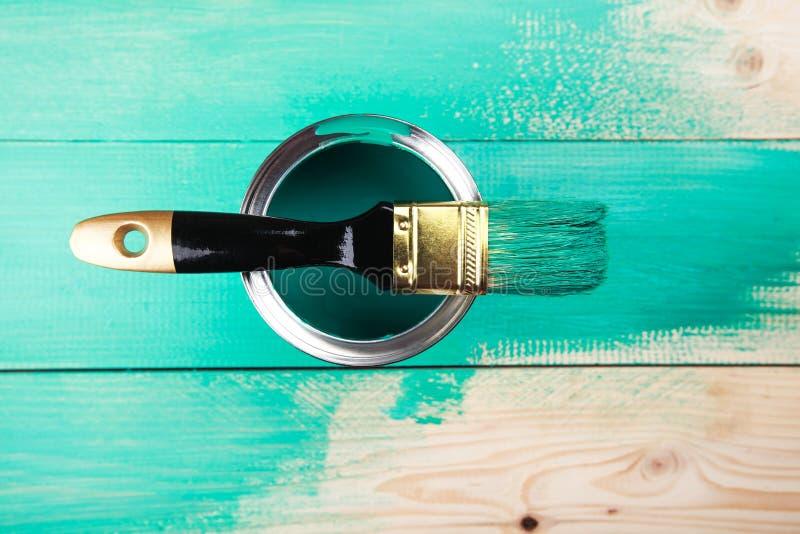 Varnishing a wooden shelf using paintbrush. Turquoise color stock image