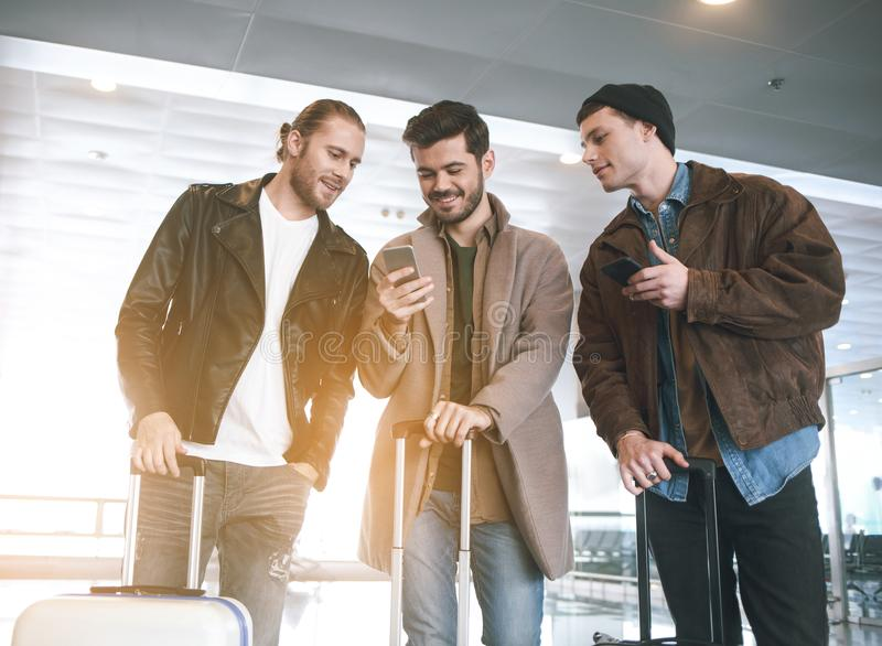 Varones felices que miran en el teléfono en el aeropuerto imagen de archivo