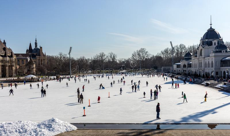 Skating people at ice rink in Varosliget park on sunny day. Winter sport and relax. stock image
