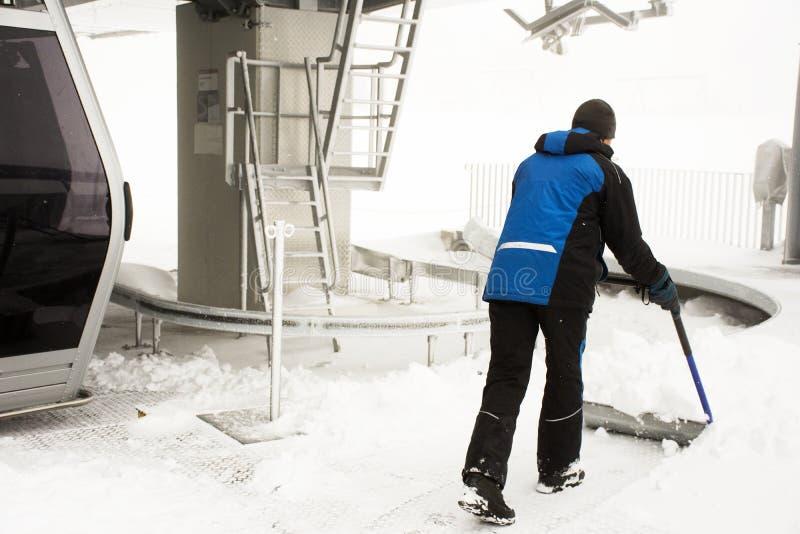 A varredura de trabalho dos povos neva na estação de transporte do teleférico de Karlesjochbahn fotos de stock royalty free