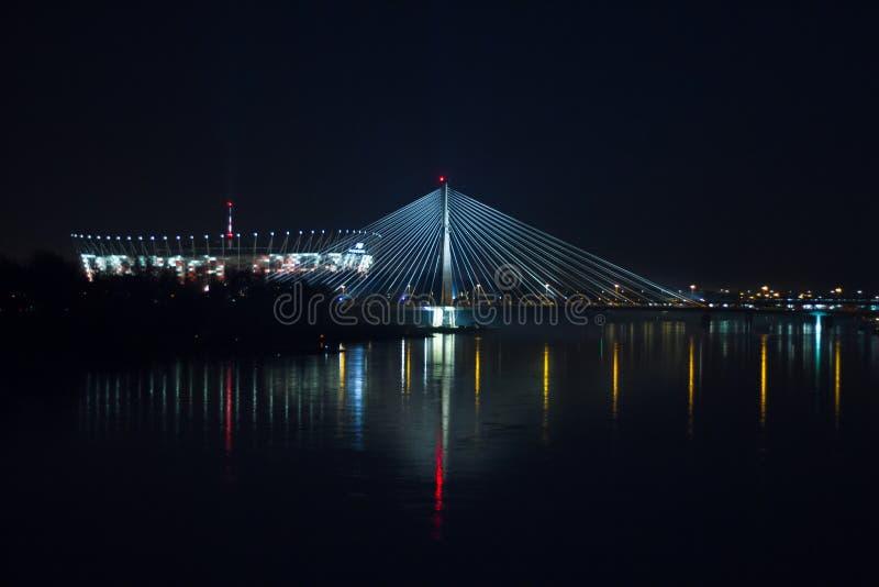 Varsóvia pelo estádio nacional de Swietokrzyski da ponte da noite e pelo Vistula River fotografia de stock