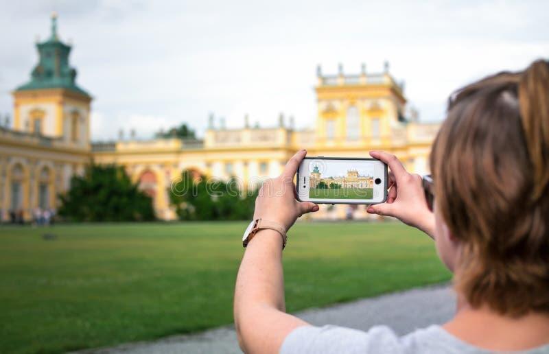 VARSÓVIA, POLÔNIA - 11 DE AGOSTO: Uma jovem mulher que fotografa o palácio real de Wilanow em Varsóvia imagem de stock royalty free