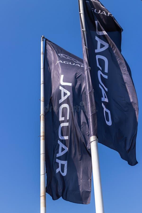 VARSÓVIA, POLÔNIA - 6 DE FEVEREIRO DE 2019: Uma bandeira com um logotipo em ondinhas de um negócio de Jaguar no vento fotografia de stock royalty free