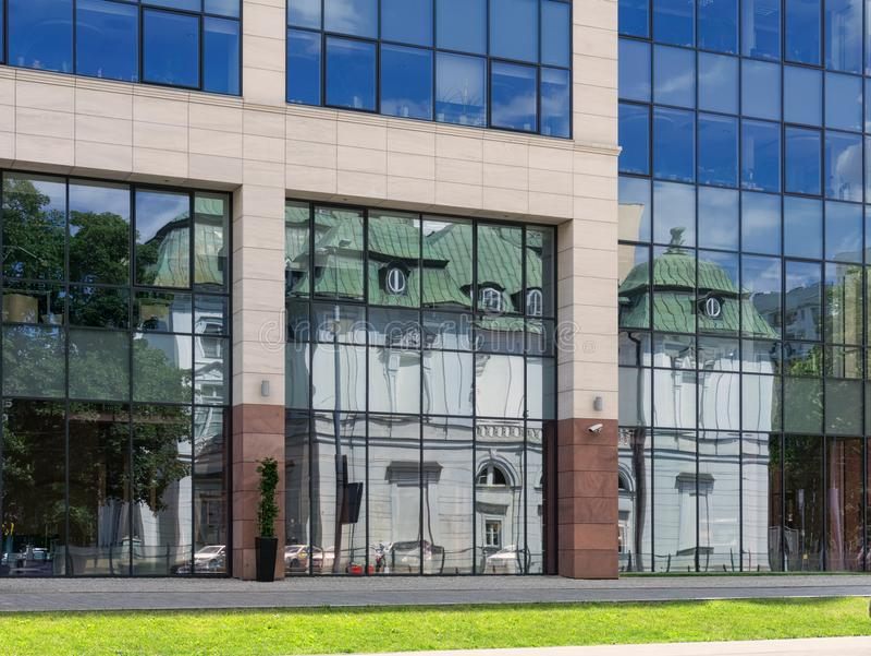 VARSÓVIA, POLÔNIA - 25 DE JUNHO DE 2015: Construção velha da reflexão na moderna fotografia de stock royalty free