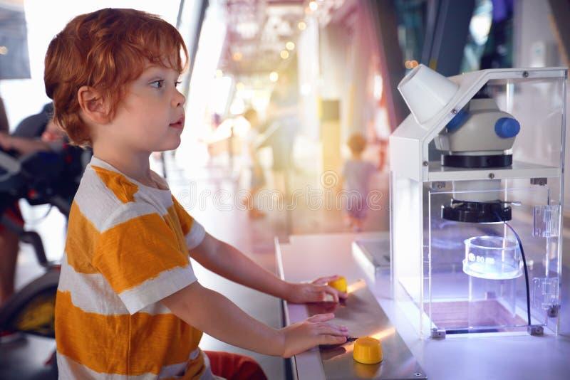 VARSÓVIA, POLÔNIA - 20 de junho de 2019: Criança que explora organismos vivos pequenos em um microscópio, centro da ciência de Co foto de stock