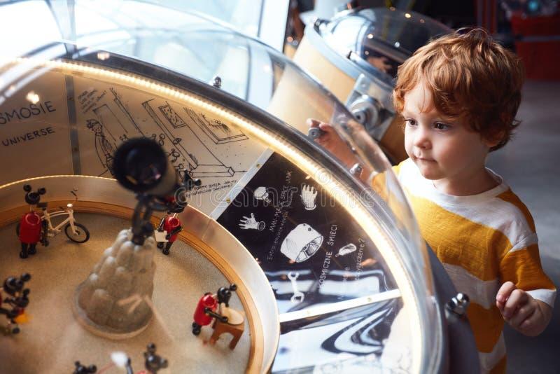VARSÓVIA, POLÔNIA - 20 de junho de 2019: Criança que testa o modelo do globo do universo no centro da ciência de Copernicus em Va imagens de stock royalty free