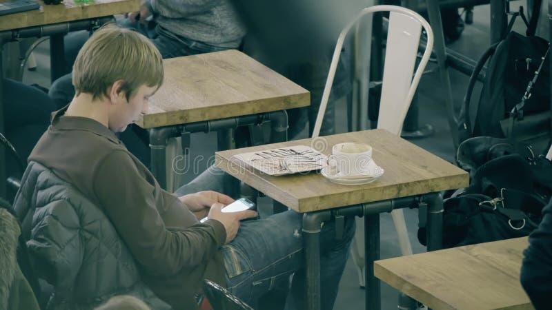 VARSÓVIA, POLÔNIA - 14 DE MARÇO DE 2018 Homem novo que usa seu smartphone em um café foto de stock