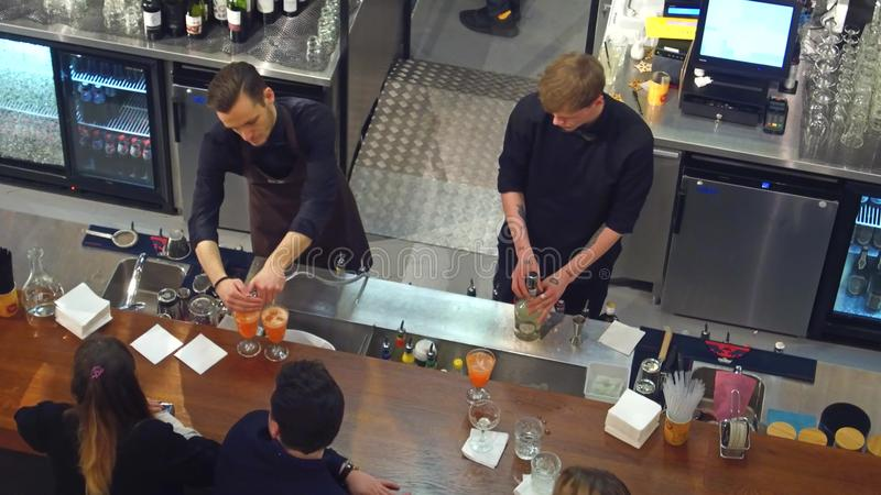 VARSÓVIA, POLÔNIA - DEZEMBRO, 22, 2016 Empregado de bar que fazem cocktail na barra Vista de cima do tiro foto de stock