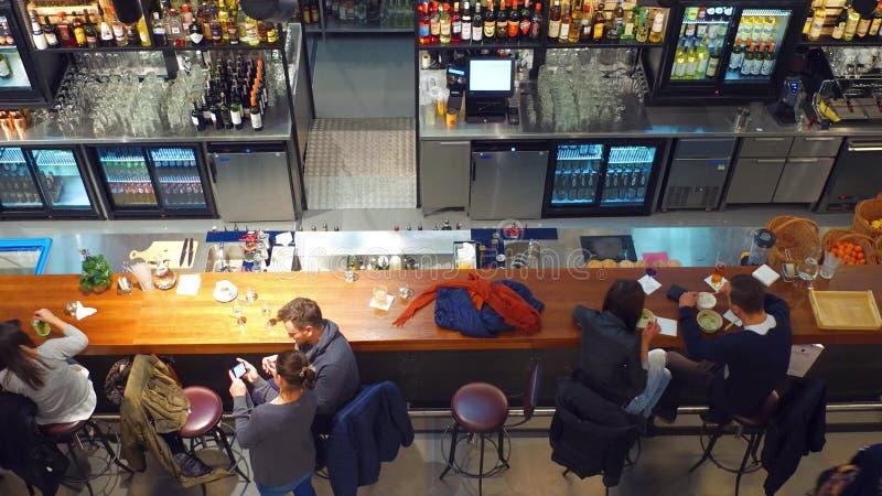 VARSÓVIA, POLÔNIA - DEZEMBRO, 17, 2016 Jovens que comem e que penduram para fora na barra Tiro da vista superior fotos de stock royalty free
