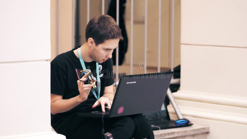 VARSÓVIA, POLÔNIA - MARÇO, 4, 2017 Homem novo que guarda seu robô de DIY e que trabalha no portátil imagens de stock royalty free