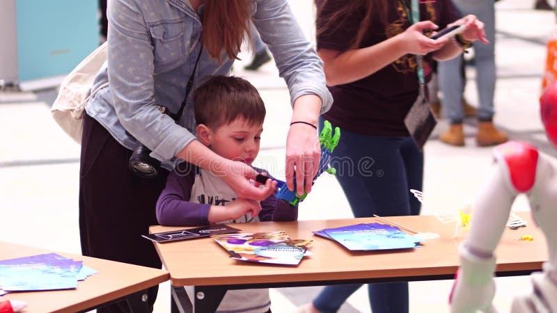 VARSÓVIA, POLÔNIA - MARÇO, 4, 2017 Mão vestindo do robô do brinquedo do rapaz pequeno fotos de stock royalty free