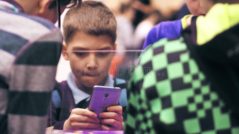 VARSÓVIA, POLÔNIA - MARÇO, 4, 2017 Menino que está na multidão e que guarda o telefone celular roxo imagens de stock