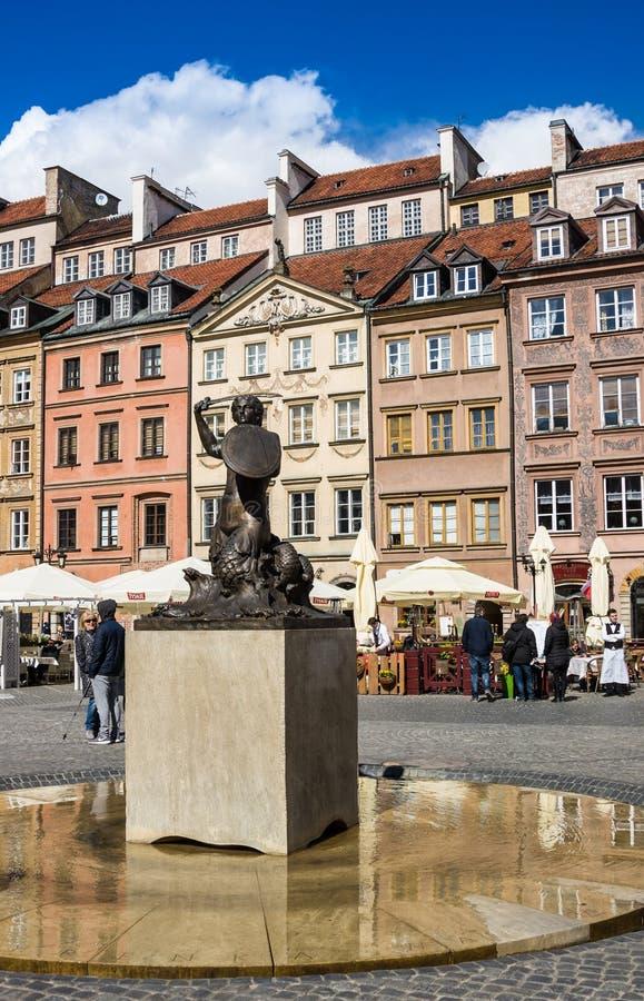 Varsóvia, Polônia - 23 de abril de 2017: Estátua da sereia Syrenka - símbolo de Varsóvia no mercado velho da cidade contra cortiç fotografia de stock royalty free