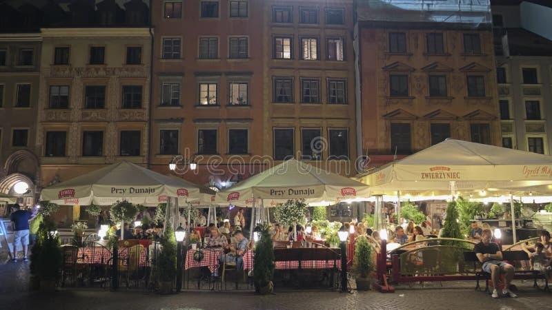 VARSAVIA, POLONIA - 4 AGOSTO 2018 Ristorante ammucchiato della via in vecchia città nella sera fotografia stock libera da diritti