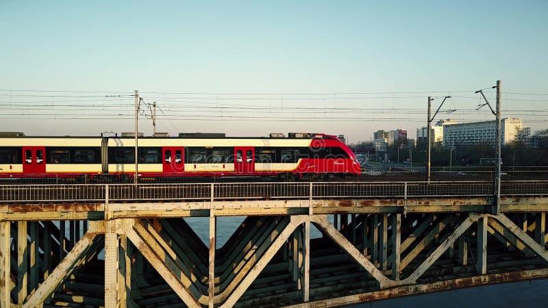 VARSAVIA, POLONIA - 27 MARZO, 2017 Colpo aereo del treno passeggeri rosso che passa ponte ferroviario attraverso il fiume immagini stock