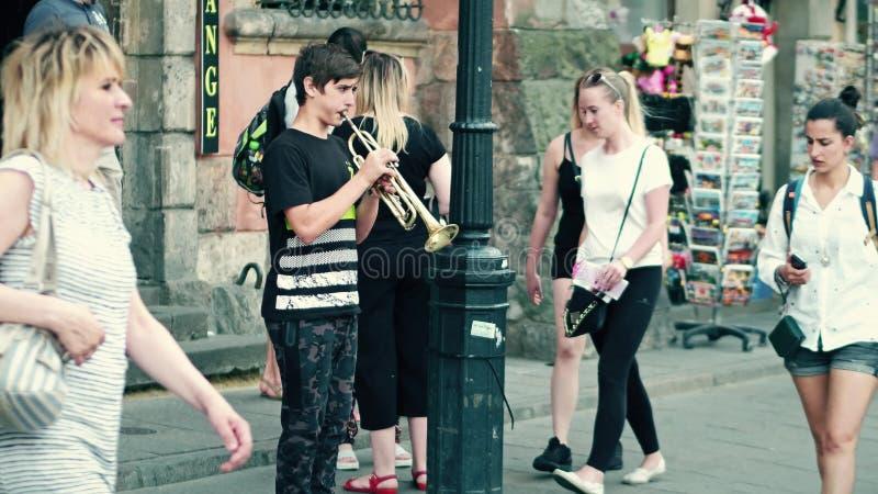 VARSOVIA, POLONIA - 10 DE JUNIO DE 2017 Muchacho que toca la trompeta en la calle fotos de archivo libres de regalías