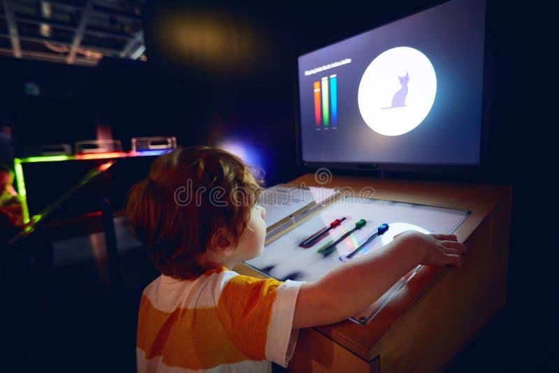 VARSOVIA, POLONIA - 20 de junio de 2019: Niño curioso que explora las características de la luz en el centro de la ciencia de Cop imágenes de archivo libres de regalías