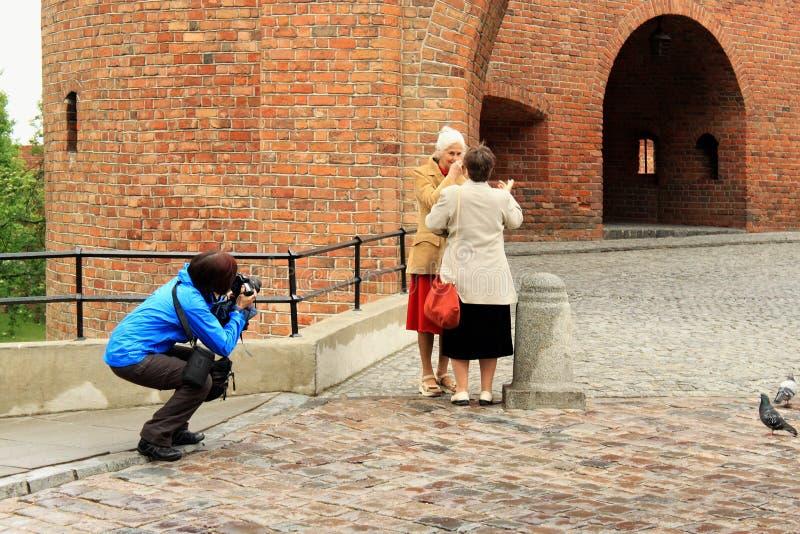 VARSOVIA, POLONIA - 12 DE MAYO DE 2012: Mujer desconocida que toma las fotos de dos mujeres mayores en el fondo con la barbacana  imágenes de archivo libres de regalías