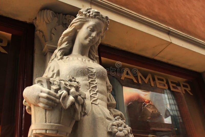 VARSOVIA, POLONIA - 12 DE MAYO DE 2012: Vieja escultura de la mujer joven cerca de la ventana del ámbar de la tienda de souvenirs foto de archivo libre de regalías