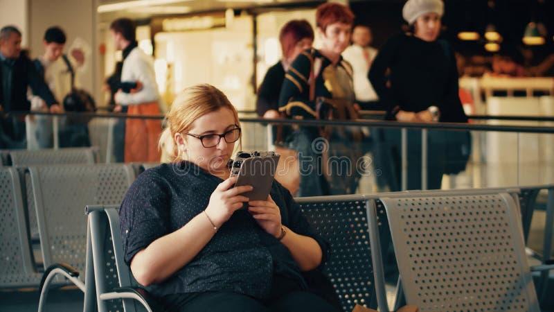 VARSOVIE, POLOGNE - AVRIL, 14, 2017 Jeune femme à l'aide de sa tablette sur le terminal d'aéroport photos libres de droits