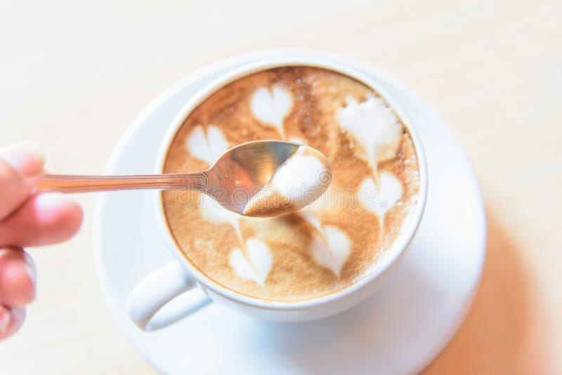 Varven mjölkar skum av kaffe vid skeden royaltyfria bilder