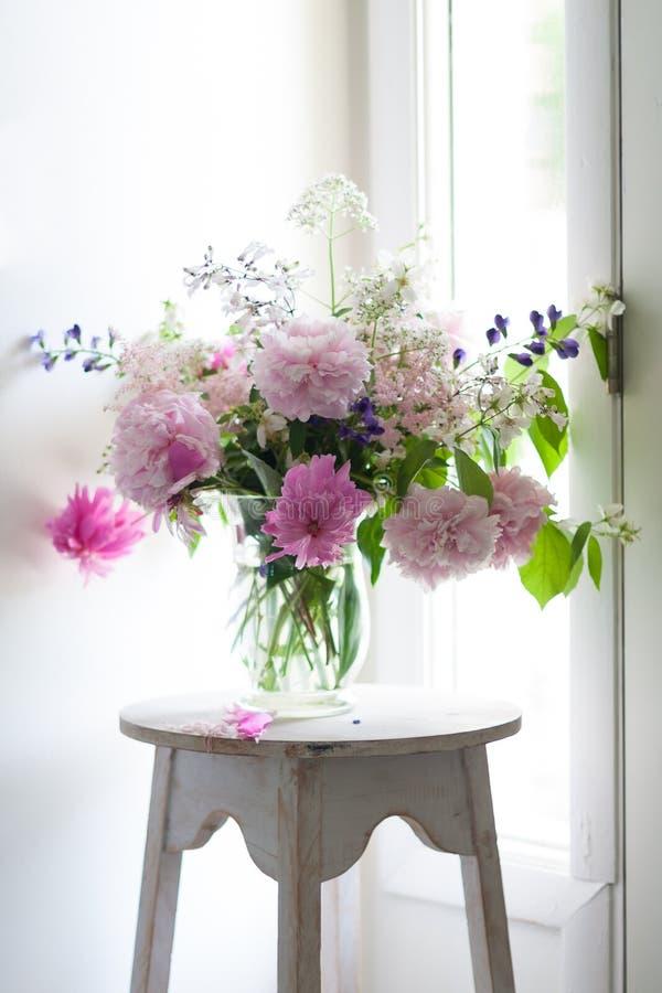 Vas av färgrika blommor i den Glass vasen fotografering för bildbyråer