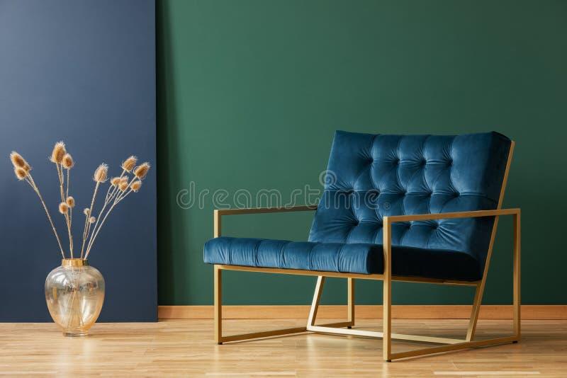 Vas bredvid fåtöljen i blå och grön elegant vardagsruminre Verkligt foto arkivbild