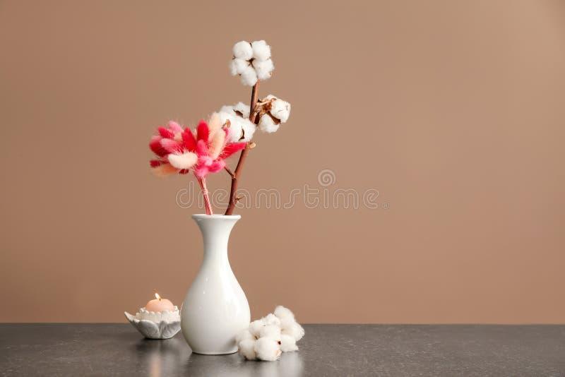 Vas med den härliga dekor- och bomullsfilialen på tabellen mot färgbakgrund royaltyfri foto