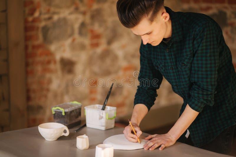Vasaio che fa ornamento sul piatto ceramico Vasaio maschio professionista estrarre una matita sul prodotto ceramico immagine stock libera da diritti