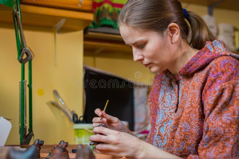 Vasaio della donna professionale che dipinge il fischio ceramico del penny del ricordo in terraglie fotografie stock libere da diritti
