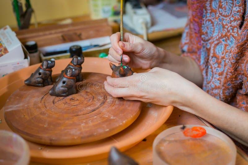 Vasaio della donna professionale che dipinge il fischio ceramico del penny del ricordo in terraglie fotografia stock