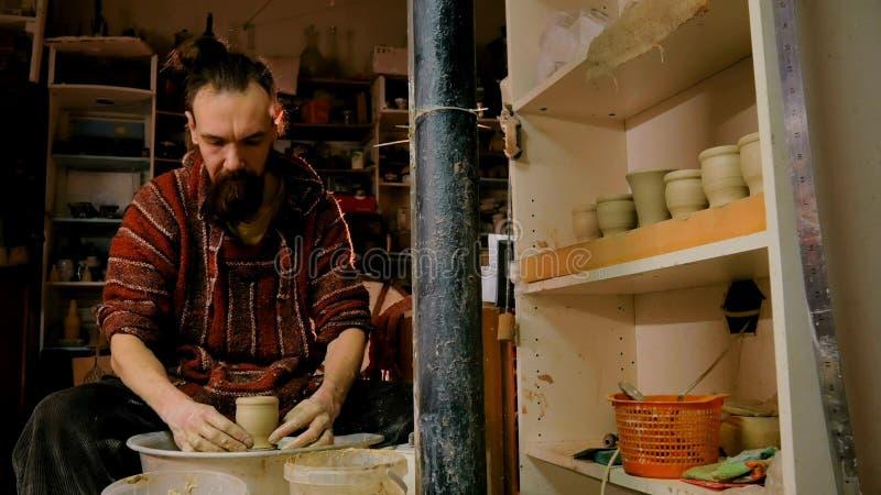 Vasaio maschio professionista che lavora con l'argilla sulla ruota del ` s del vasaio fotografia stock libera da diritti