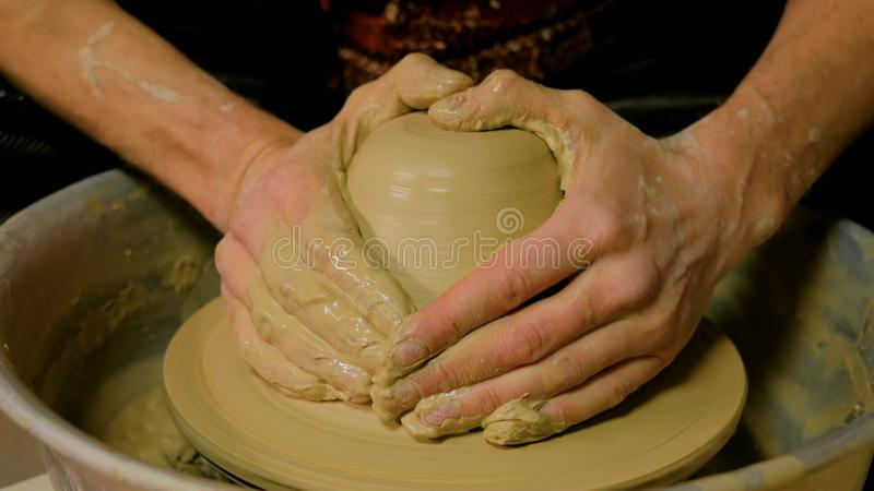 Vasaio maschio professionista che lavora con l'argilla sulla ruota del ` s del vasaio fotografie stock