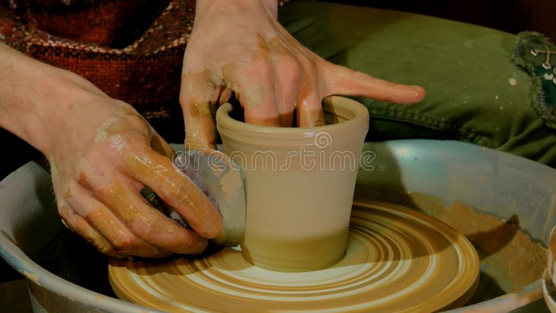 Vasaio professionista che modella tazza con l'utensile speciale nell'officina delle terraglie fotografie stock