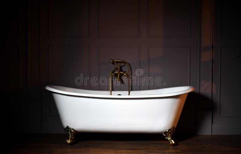Vasca bianca del piede dell'artiglio di bello stile classico con il rubinetto antiquato e lo spruzzatore dell'acciaio inossidabil fotografie stock
