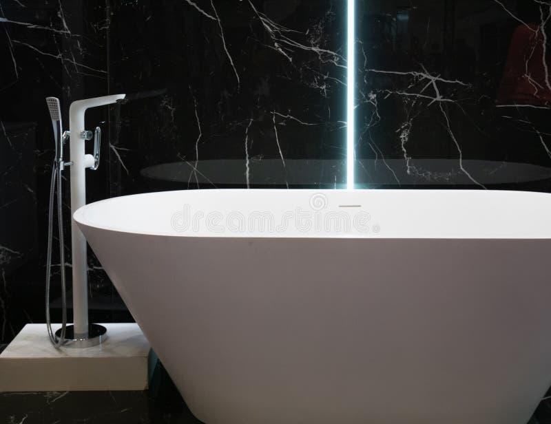 Vasca bianca moderna all'appartamento dell'hotel con la parete di marmo nera su fondo interior design contemporaneo al bagno fotografie stock libere da diritti