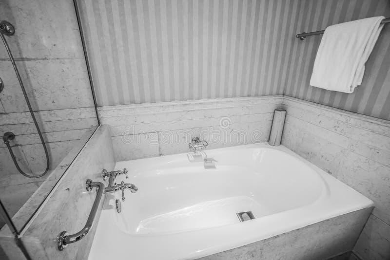 Vasca in bianco e nero con il rubinetto e l'asciugamano di lusso per il bagno nell'hotel immagini stock