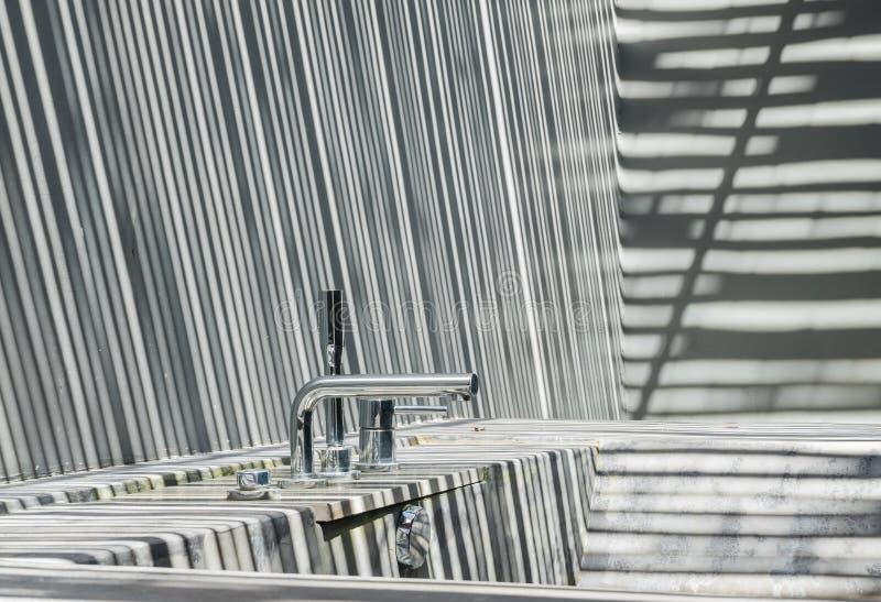 Vasca concreta con il rubinetto d'argento su luce solare nel pomeriggio fotografia stock