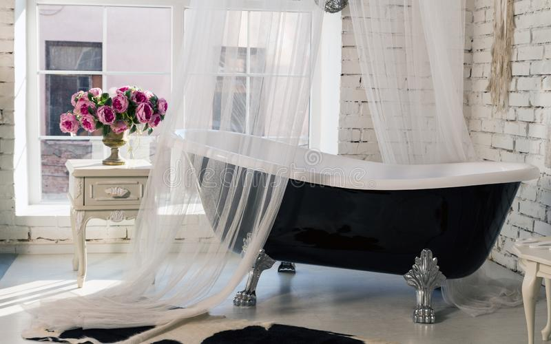 Vasca nera d'annata classica nella stanza di stile del sottotetto fotografie stock