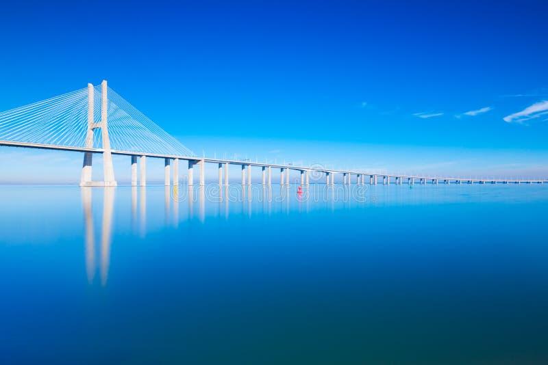 Vasco da Gama Bridge op water, Lissabon, Portugal wordt weerspiegeld dat stock foto's