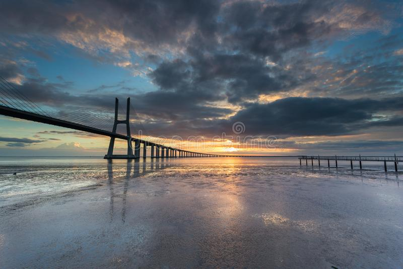 Long bridge over tagus river in Lisbon at sunrise royalty free stock photos
